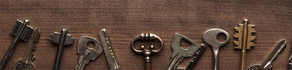 Many different classic keys on a dark brown wooden table