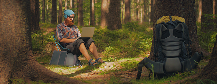 man-using-a-laptop-outdoors-during-a-camping-trip--PAZQXJK